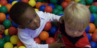 Two boys playing in a plastic ball pit